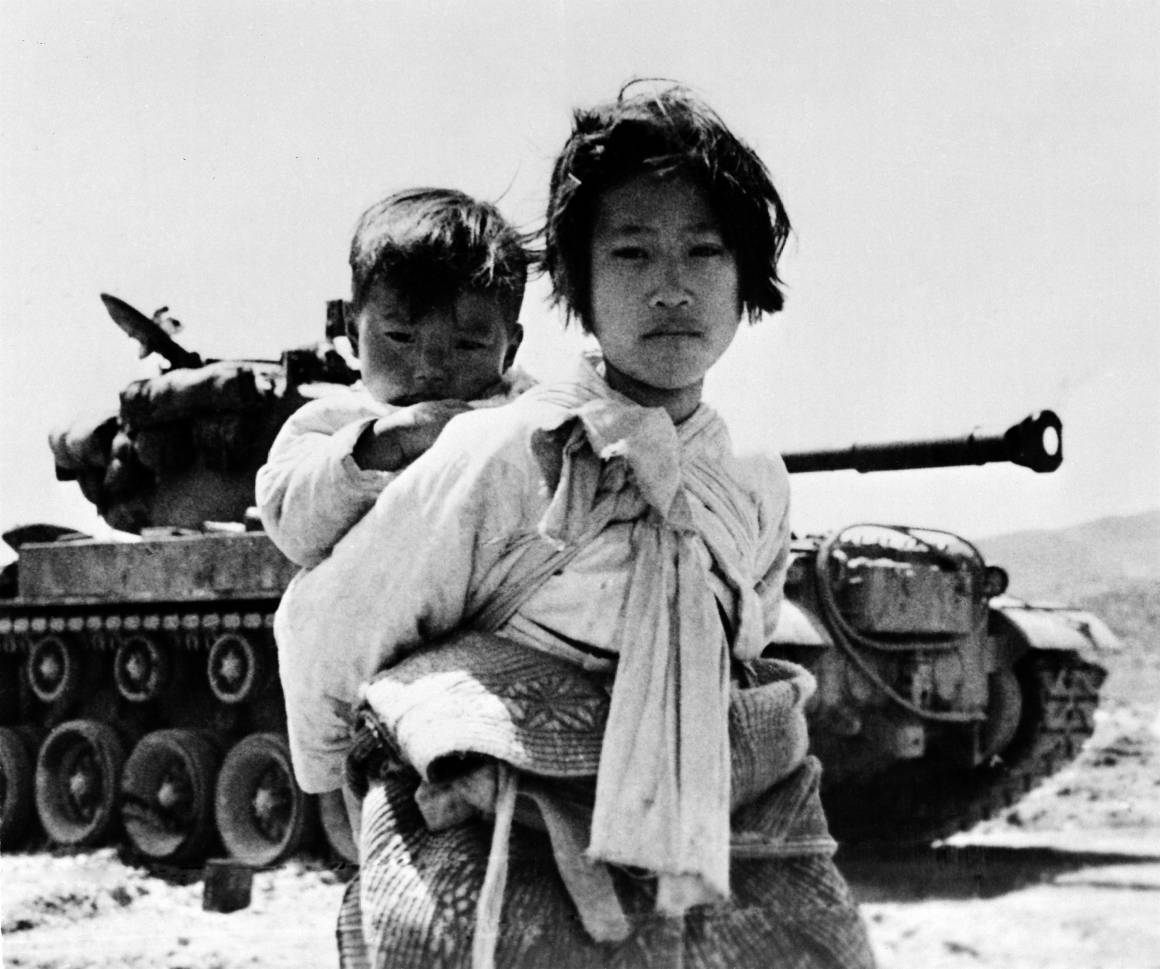 Yhdeksänvuotias tyttö kantaa pikkuveljeään. Kuva tästä karkuteillä jääneestä orvoksi jääneestä sisaruspariskunnasta on otettu Korean sodan aikana, 9. kesäkuuta 1951. Kuva: YK-kuva/Yhdysvaltain laivasto.