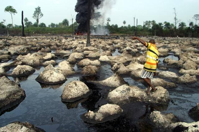 En mann går i det ødelagte miljøet etter oljeutslipp.  Foto: IRIN Photo