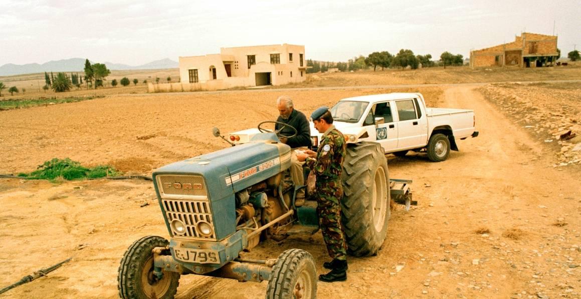 YK:n rauhanturvaaja tarkistaa kyproslaisen maaviljelijän henkilötodistuksen. Kuva: UN Photo/John Isaac