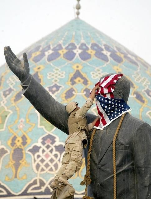 Sotilas peittää Saddam Husseinia esittävänpatsaankasvot Yhdysvaltain lipulla. Kuva: AP Photo/Laurent Rebours/Flickr
