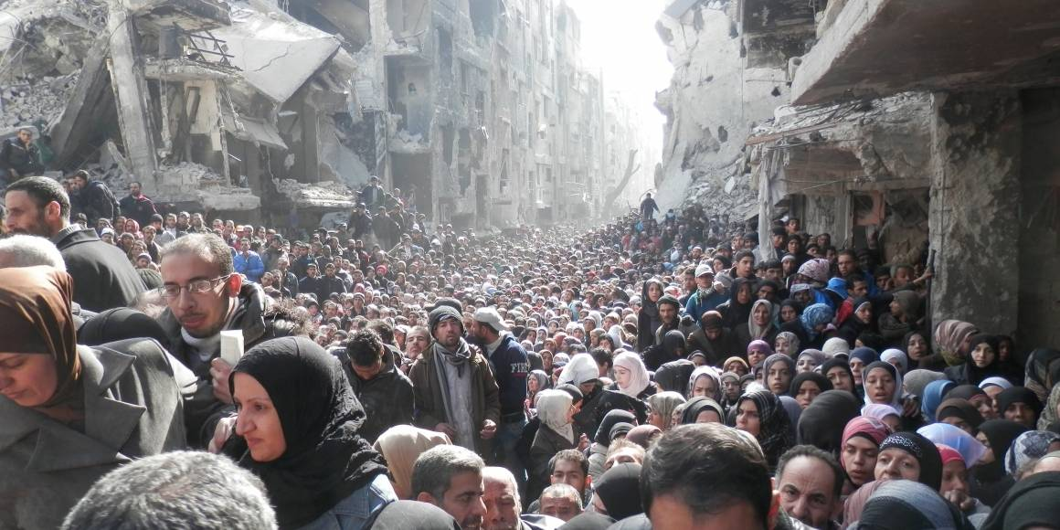 Syyrialaiset pakolaiset jonottavat YK:n toimittamaa ruoka-apua Yarmoukin pakolaisleirillä lähellä Damaskosta (tammikuu 2014). Kuva: Zuma Press/UNRWA