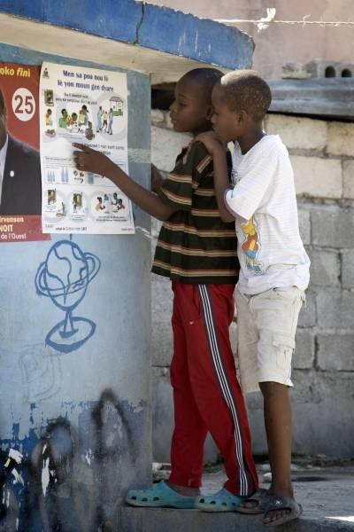 Lapset tutkivat Post-au-Princessä julistetta, jossa kerrotaan,mittenkoleraltavoi suojautua. Kuva:UN Photo/UNICEF/Marco Dormino