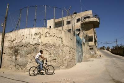 Poika Aidan pakolaisleirillä Betlehemissä pyöräilemässä ympäri israelilaisten muuria. Muuri estää Länsirannan palestiinalaisia liikkumasta vapaasti Israelin ja Palestiinan välillä. 2003, UN Photo/Stephenie Hollyman.